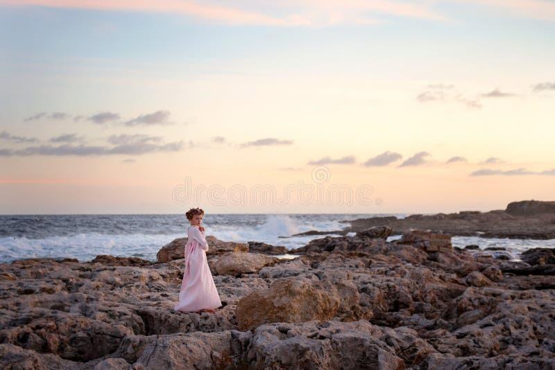 Soluppgången målar med ljusa färger himlen över den steniga kusten av havhavet som står på en flicka i långa wi för en rosa färgk royaltyfri bild