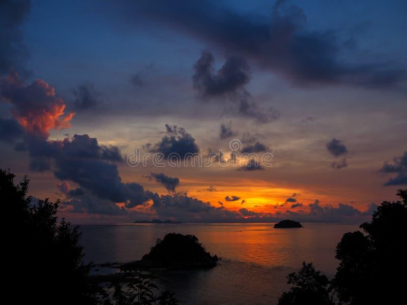Soluppgånghavssikt med den små ön och skuggor av den orange himmelthroen royaltyfri bild