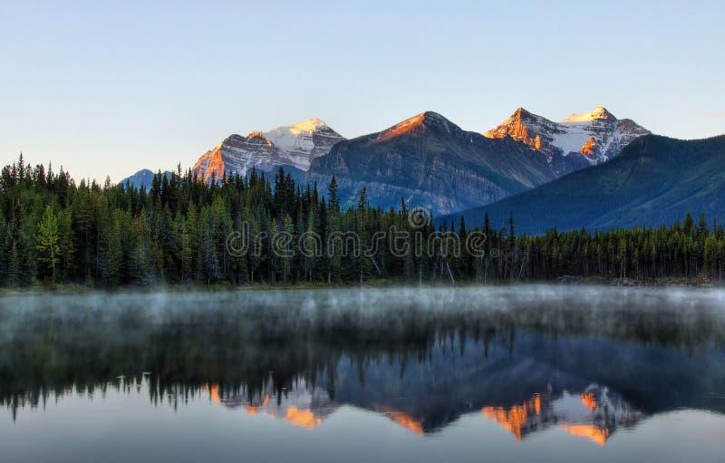 Soluppgångreflexion i bergen arkivfoto