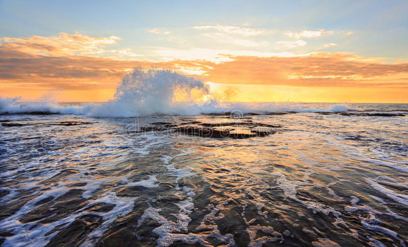 Soluppgångseascapefärgstänk i formen av en våg royaltyfria foton