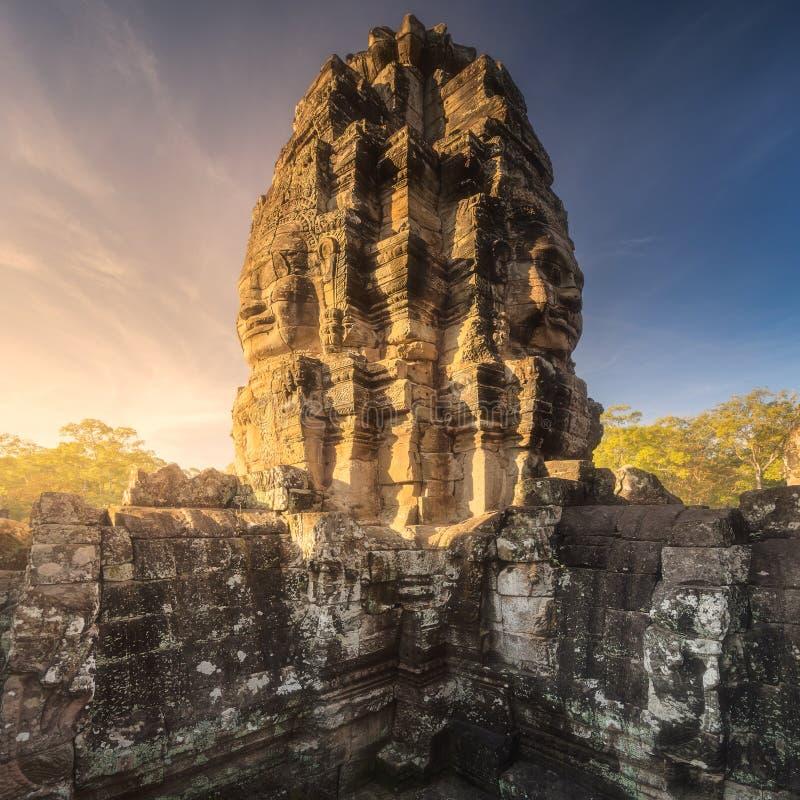Soluppgångsikten av den forntida templet Bayon Angkor med stenen vänder mot Siem Reap, Cambodja arkivfoto