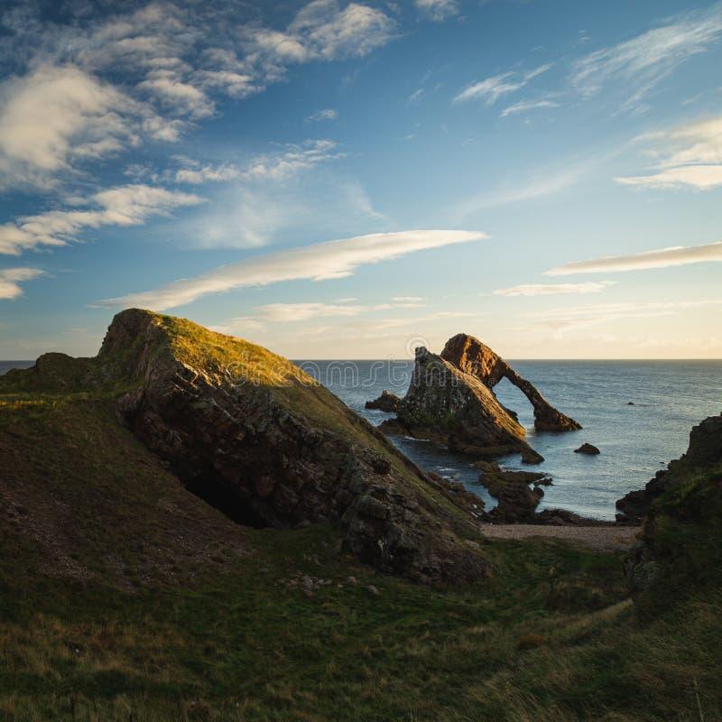 Soluppgångtid vid pilbågen Fiddle Rock i Skottland royaltyfria foton