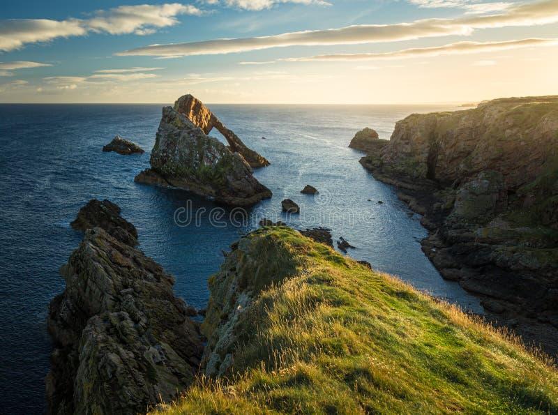 Soluppgångtid vid pilbågen Fiddle Rock i Skottland royaltyfria bilder
