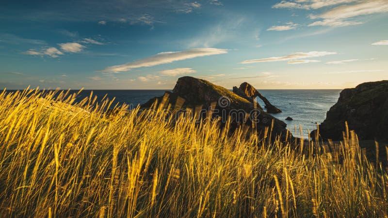 Soluppgångtid vid pilbågen Fiddle Rock i Skottland royaltyfri foto