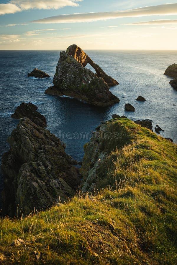 Soluppgångtid vid pilbågen Fiddle Rock i Skottland arkivbilder