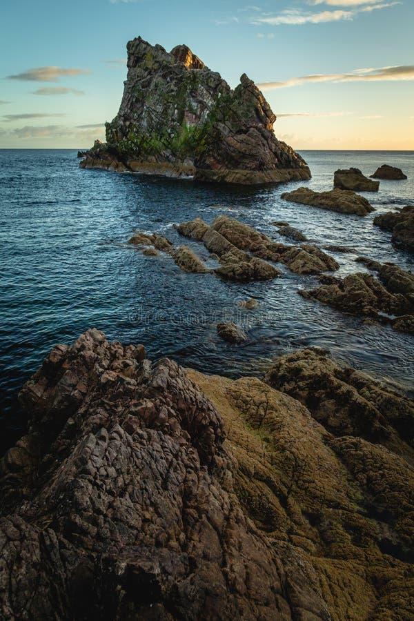 Soluppgångtid vid pilbågen Fiddle Rock i Skottland arkivfoto