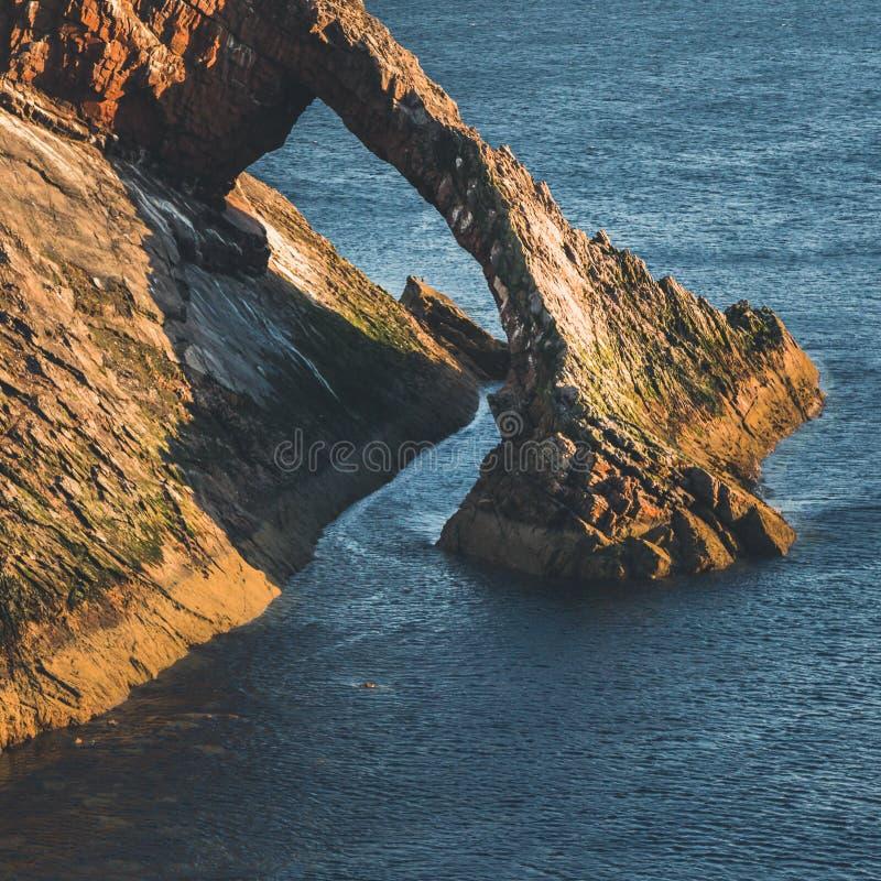 Soluppgångtid vid pilbågen Fiddle Rock i Skottland arkivfoton