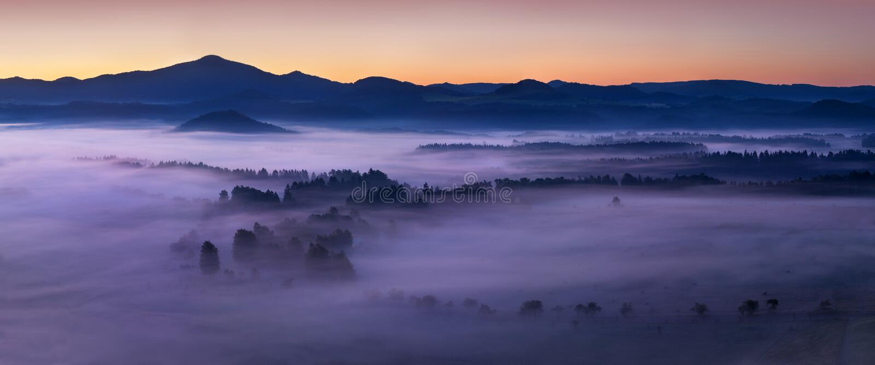 Soluppg?ng ?ver Misty Landscape Scenisk sikt av dimmig morgonhimmel med resningsolen ovanf?r Misty Forest royaltyfria bilder