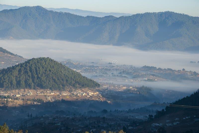 Soluppg?ngberg odlade med pittoreska byar i lantliga Guatemala, mist och frost Central America arkivbild