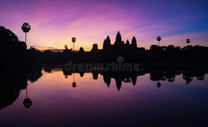 Soluppg?ngsikt av den popul?ra forntida templet komplexa Angkor Wat f?r turist- dragning med reflekterat i sj?n Siem Reap, Cambodj royaltyfri foto