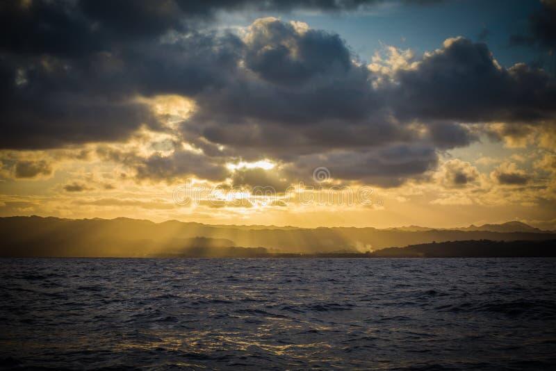 Soluppsättning över öberg från havet royaltyfri bild
