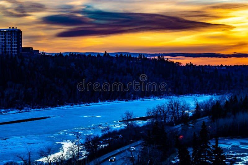 Solupps?ttningar ?ver vinterstad Djupfrysta River Valley royaltyfri bild