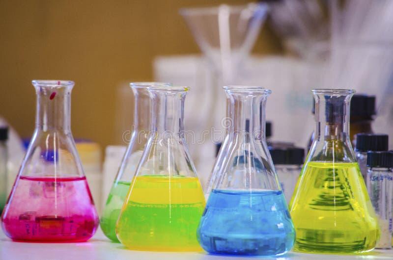 Solution colorée multiple dans la fiole conique sur un banc dans un laboratoire de chimie avec l'expérience de chimie organique d photos stock