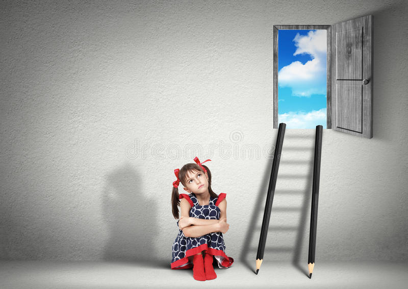 Solution concept, child girl dreaming near stairs of pencils stock photography