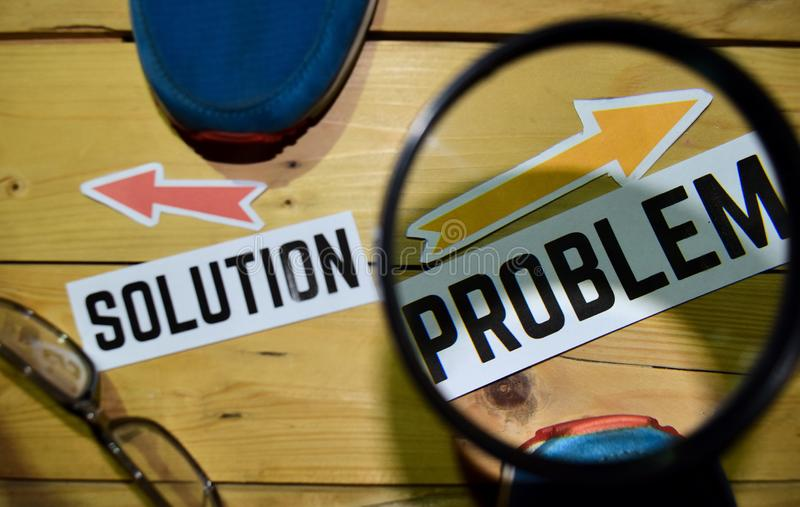 Solution or Problem opposite direction signs in magnifying with sneakers and eyeglasses on wooden. Vintage background. Business, education and finance concepts royalty free stock photography