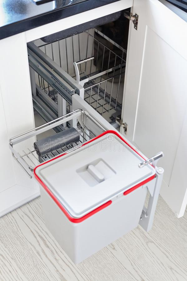 Solution for storing the trash can in the kitchen cupboard under stock photography