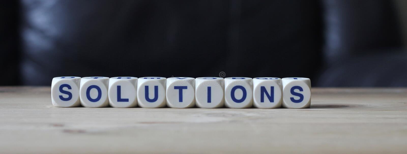 Solutions. Letters cube wordings on wood background royalty free stock image