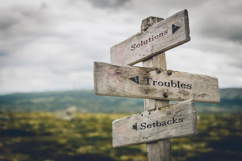 Solutions, troubles and setbacks signpost. Solutions, troubles and setbacks text on wooden signpost outdoors in nature. Business, corporate, leadership concept stock images