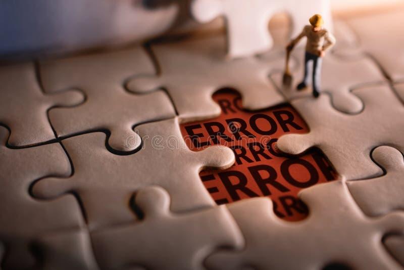 Soluzione che risolve concetto di problema un messaggio di errore trovato uomo miniatura del lavoratore su un pezzo di puzzle fotografia stock