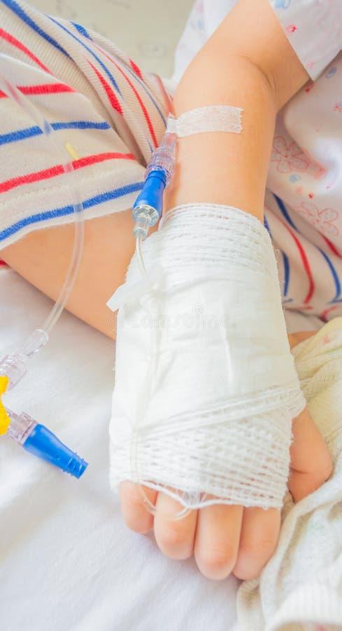 Soluzione IV in mano dei pazienti di un bambino immagini stock