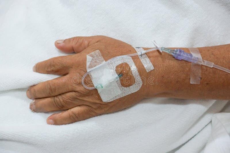 Soluzione IV in una mano dei pazienti immagini stock
