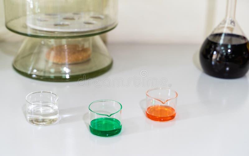 Soluzioni liquide chimiche variopinte in boccette di vetro sul piano di lavoro bianco del laboratorio immagini stock