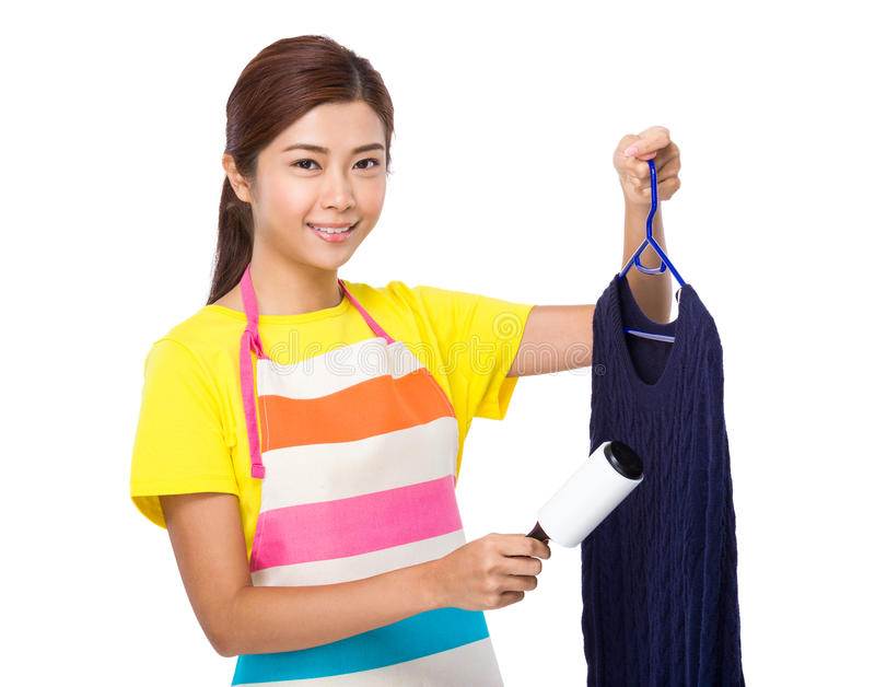 Solvant asiatique de la poussière d'utilisation de femme au foyer sur des tricots photographie stock