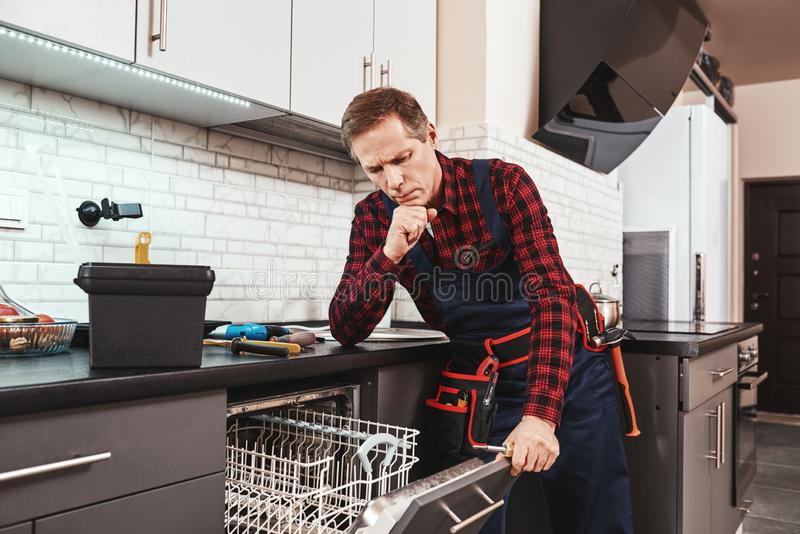 Solve the problem. Male technician think about fixing dishwasher stock photos