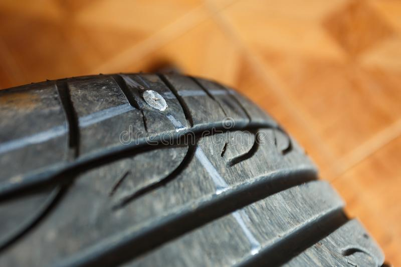 Tires leak because the nail pounding,replacement repair fixing car`s tire trying to remove nail from hole. Flat tire. punctu. Solve problem wheel in garage auto stock photos