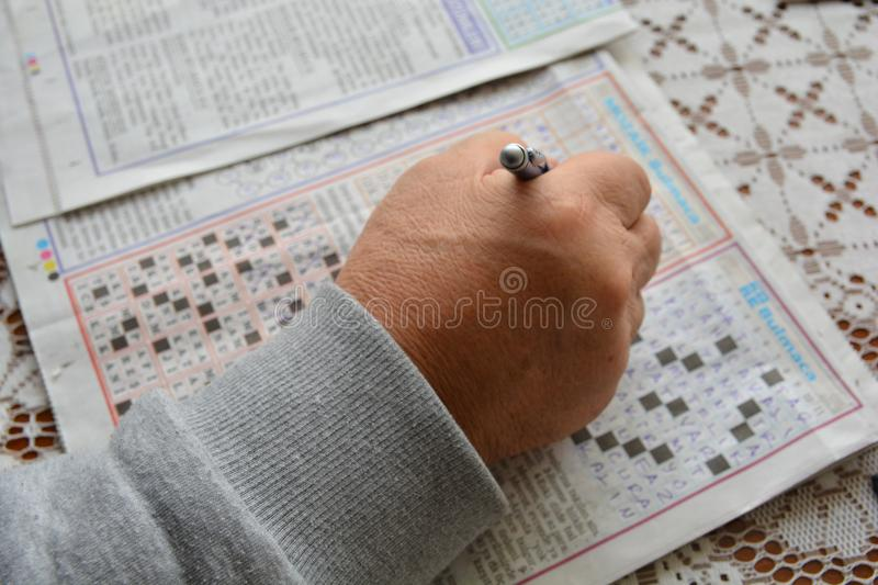Solve puzzles. Old man hands. He holds a pencil in his hand. solving puzzles royalty free stock photos