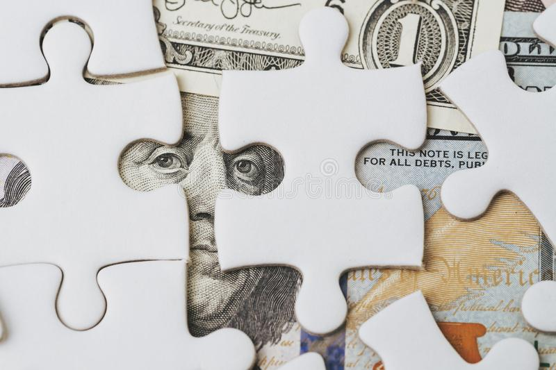 Solving the financial or business problem or idea for making money concept, white jigsaw puzzle game on US Dollar banknote with royalty free stock images
