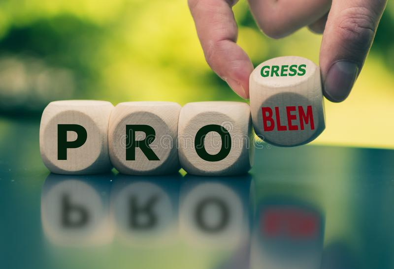 Solving a problem and making progress. Hand flips a cube and changes the word `problem` to `progress` royalty free stock photo