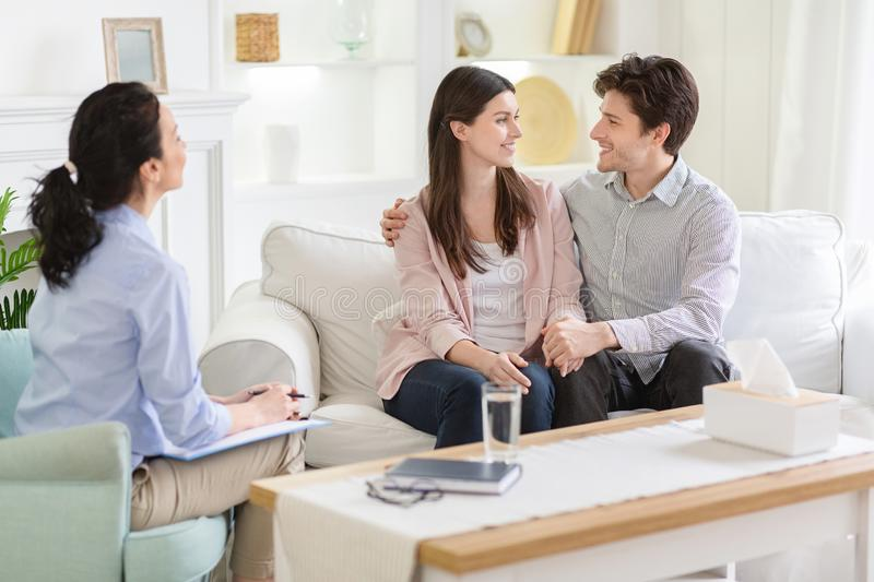 Happy couple at successful therapy session with family psychologist royalty free stock photo