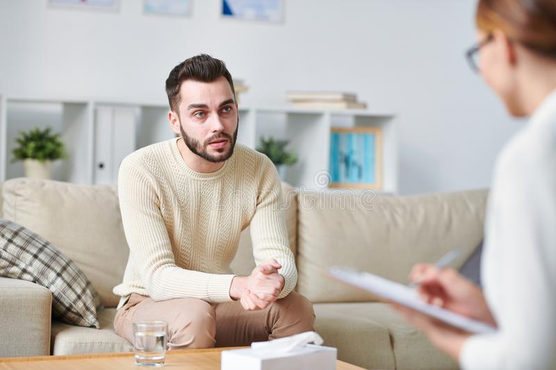 Solving psychological problem. Casual bearded young men looking at counselor while listening to her advice and explaining his troubles stock image