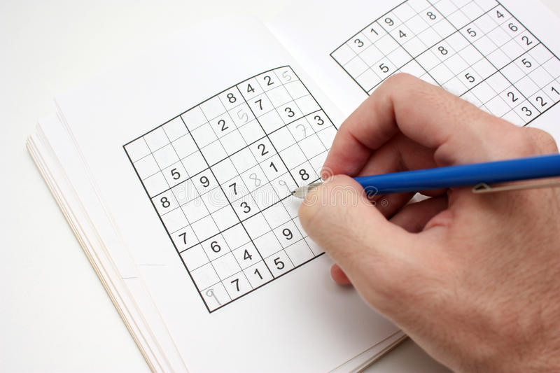 Solving a SUDOKU puzzle. Image of an open SUDOKU book, with a puzzle being solved royalty free stock photography
