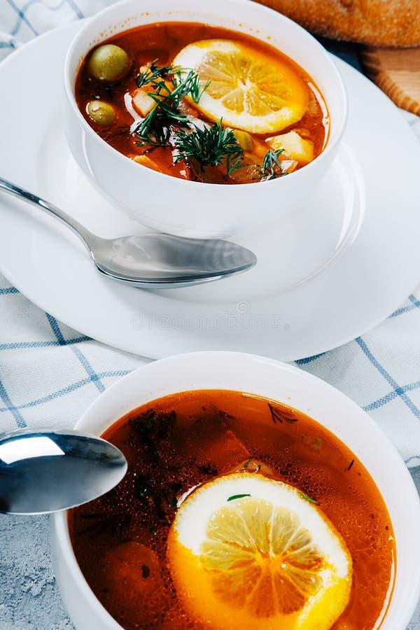 Solyanka en tjock soppa av grönsaker och kött som tjänas som med citronen och oliv royaltyfri foto