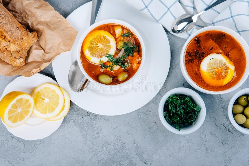 Solyanka en tjock soppa av grönsaker och kött som tjänas som med citronen och oliv arkivfoton