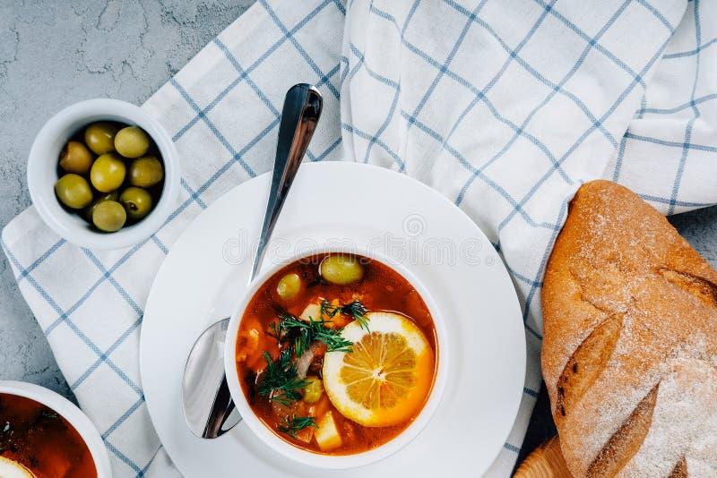 Solyanka en tjock soppa av grönsaker och kött som tjänas som med citronen och oliv royaltyfri fotografi