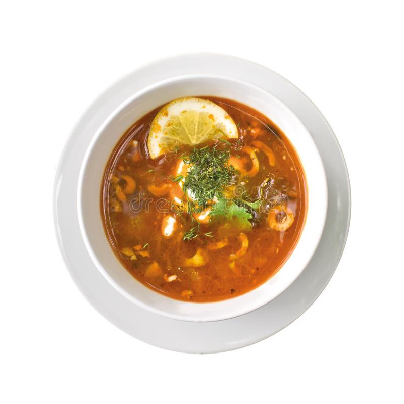 Solyanka soup in the plate, isolated on white background. Top view royalty free stock photography