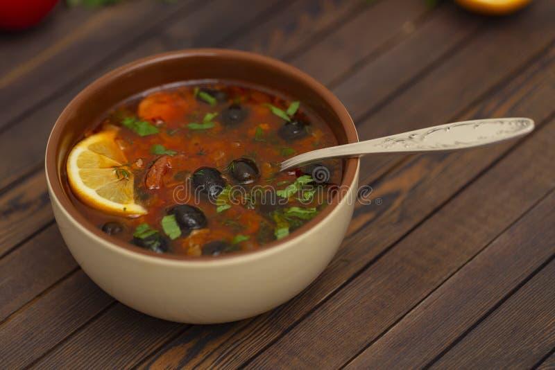Solyanka-Suppe mit Zitrone, Fleisch, Essiggurken, Tomatensauce und traditionellem russischem Teller Solyanka der Oliven stockfotos