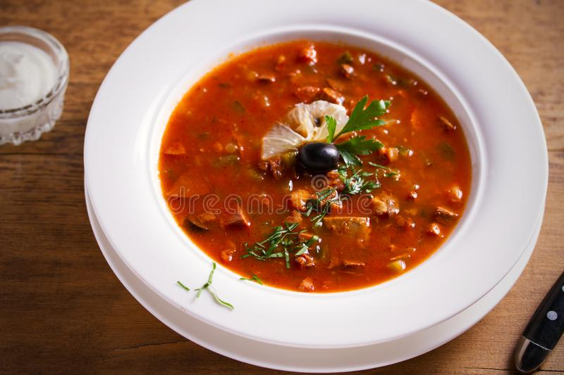 Solyanka - thick, spicy and sour Russian soup, made of beef, ham, sausages, chicken breast cucumber pickles and tomatoes. stock photos