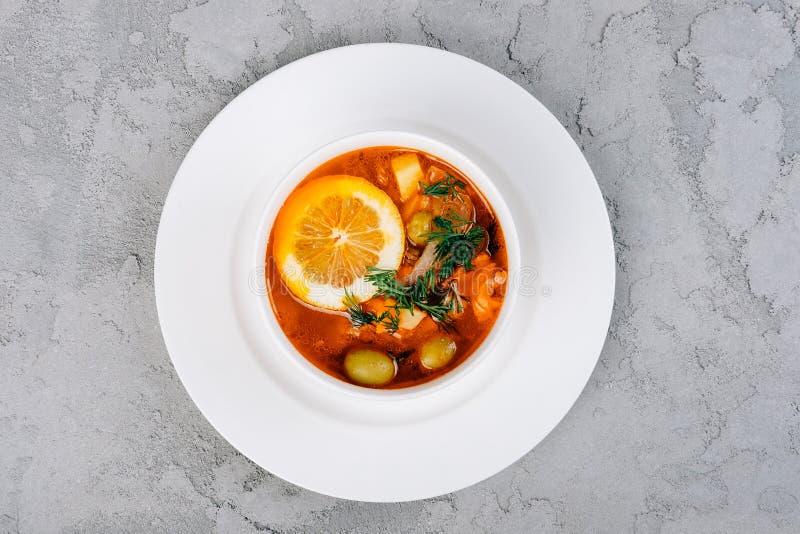 Solyanka una minestra spessa delle verdure e della carne servite con il limone e le olive fotografie stock libere da diritti
