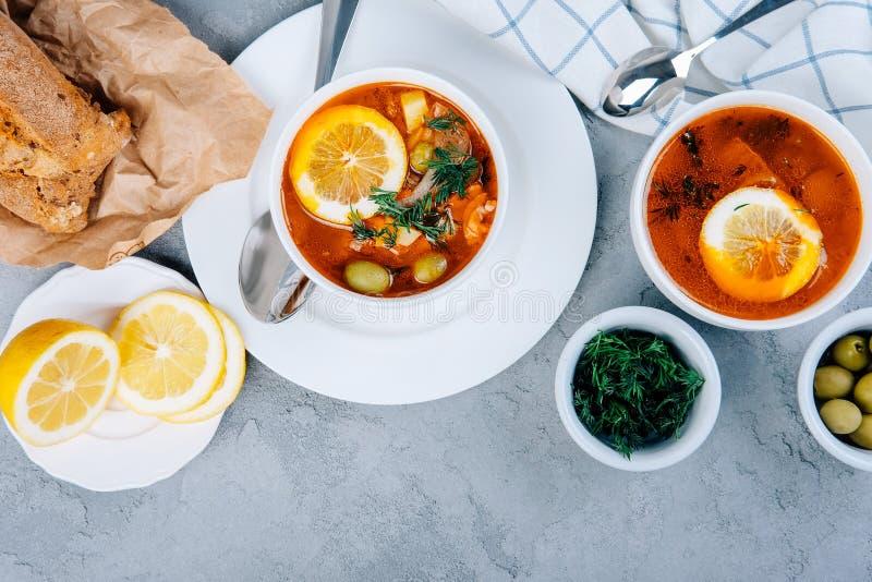 Solyanka una minestra spessa delle verdure e della carne servite con il limone e le olive fotografie stock