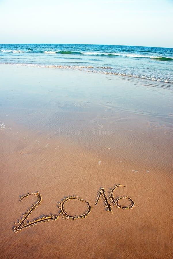 2016 som är skriftlig i sand på den tropiska stranden arkivfoton