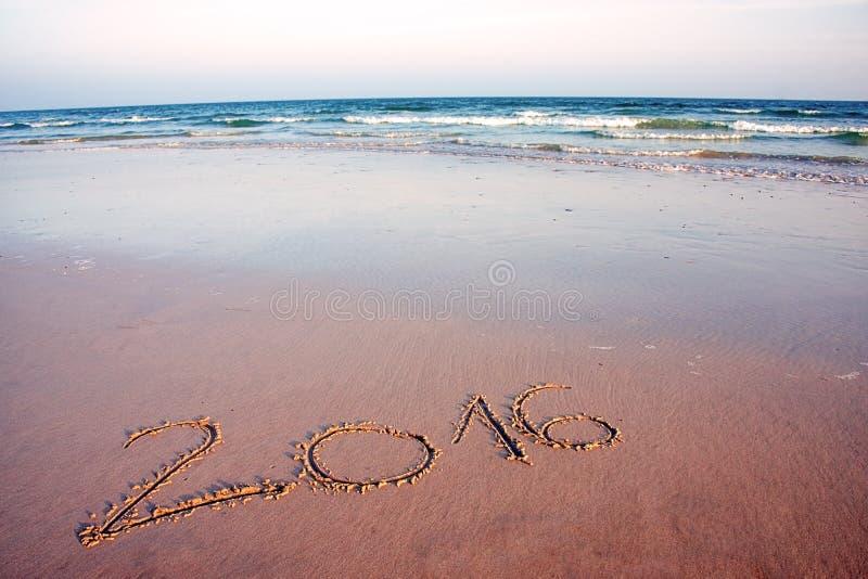 2016 som är skriftlig i sand på den tropiska stranden, i solnedgång arkivfoto