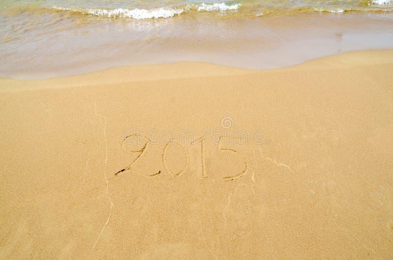 2015 som är skriftlig i sanden arkivfoto