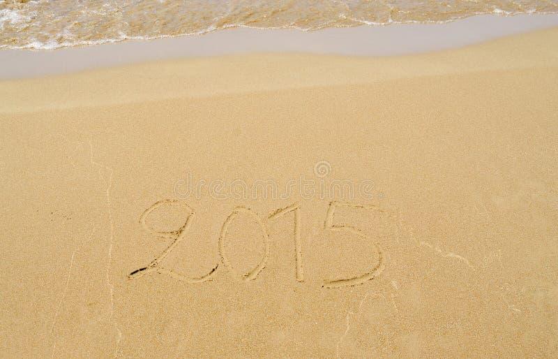 2015 som är skriftlig i sanden fotografering för bildbyråer