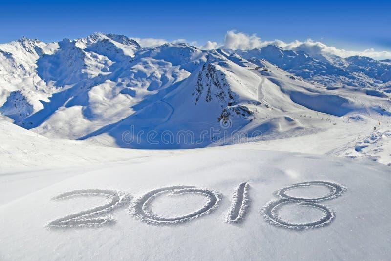 2018 som är skriftlig i snön, berglandskap i bakgrunden royaltyfri bild