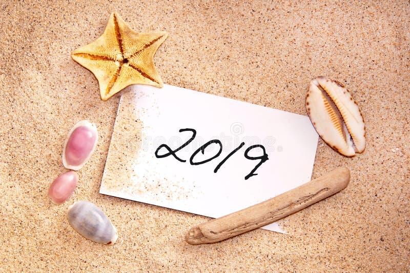 2019 som är skriftlig på en anmärkning i sanden med snäckskal arkivbild