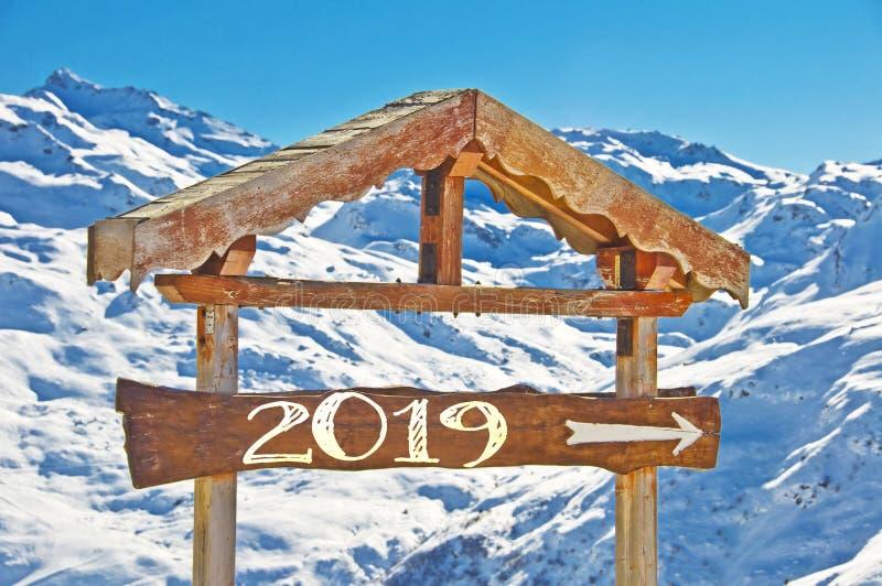 2019 som är skriftlig på ett träriktningstecken, snöberglandskap på bakgrunden arkivfoto